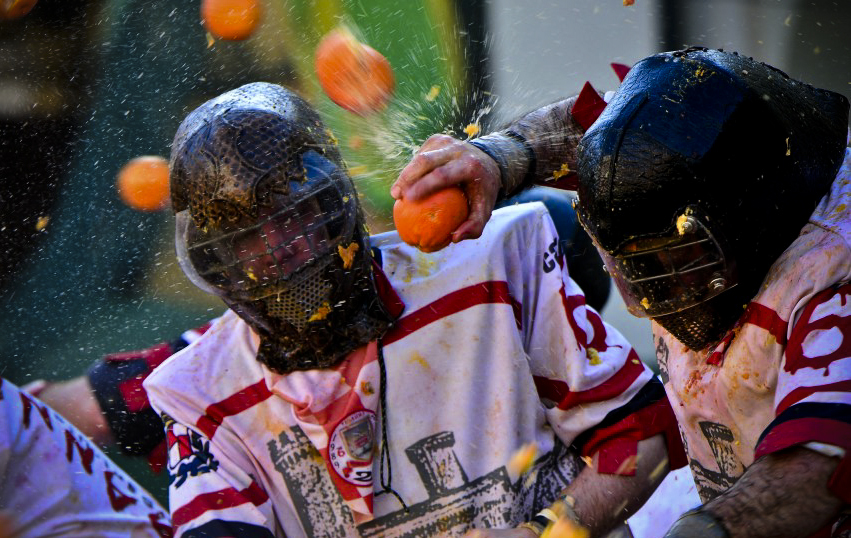 "Men with helmets are hit by oranges during the traditional ""battle of the oranges"" held during the carnival in Ivrea, near Turin, on March 4, 2014. During the event which marks the people's rebellion against tyrannical lords who ruled the town in the Middle Ages, revellers parading on floats represent guards of the tyrant, while those on foot the townsfolk. AFP PHOTO / GIUSEPPE CACACE (Photo credit should read GIUSEPPE CACACE/AFP/Getty Images)"